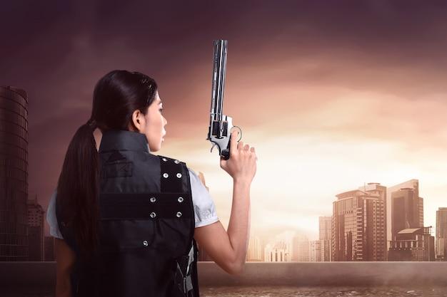 Hintere ansicht der sexy asiatischen frau, die polizeiuniform mit gewehr verwendet