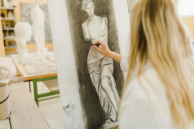 Hintere ansicht der skizzierenden skulptur des blonden weiblichen künstlers auf segeltuch
