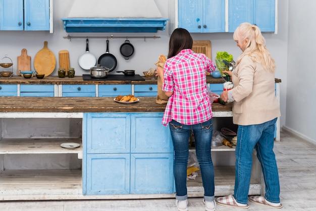 Hintere ansicht der tochter und ihrer älteren mutter, die lebensmittel in der küche zubereiten