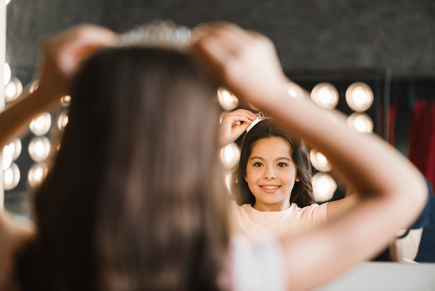 Hintere ansicht der tragenden krone des mädchens auf seinem kopf, der im spiegel schaut