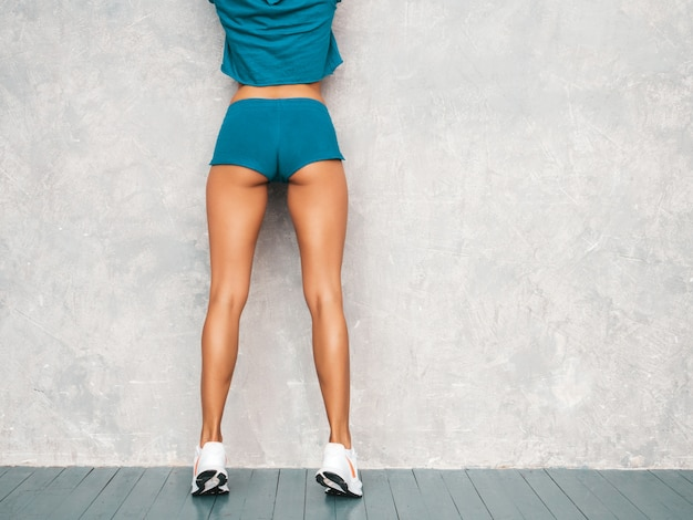 Hintere ansicht der überzeugten eignungsfrau in der sportkleidung, die überzeugt schaut junge weibliche tragende sportkleidung. schönes modell mit perfektem gebräuntem körper frau, die im studio nahe grauer wand aufwirft