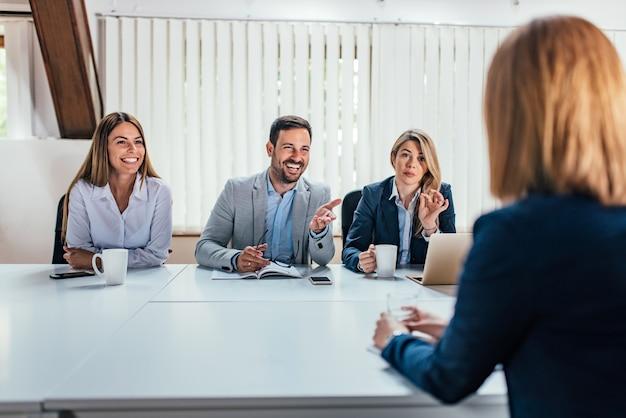 Hintere ansicht der weiblichen person, die erfolgreiches geschäftstreffen mit stunde managern hat.