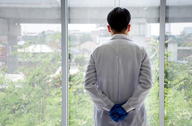 Hintere ansicht des asiatischen doktors stehend mit den händen umklammert hinter ihrer rückseite