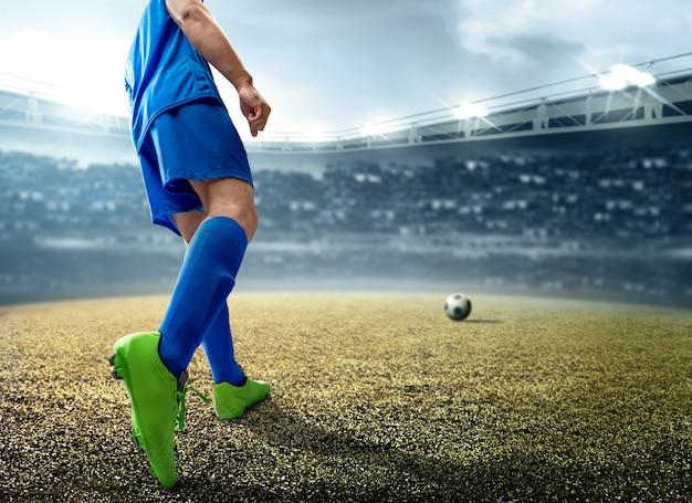 Hintere ansicht des asiatischen fußballspielermannes, der den ball auf dem fußballplatz tritt