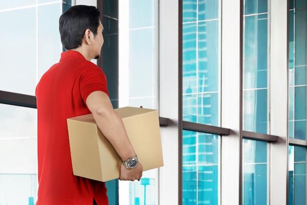 Hintere ansicht des asiatischen männlichen kuriers, der das paket hält