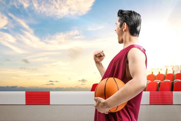Hintere ansicht des asiatischen mannbasketballspielers, der den ball mit einem aufgeregten ausdruck hält