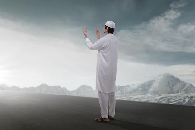 Hintere ansicht des asiatischen moslemischen betenden mannes