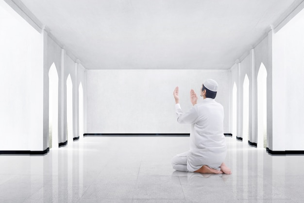 Hintere ansicht des asiatischen moslemischen mannes kniend und zum gott betend