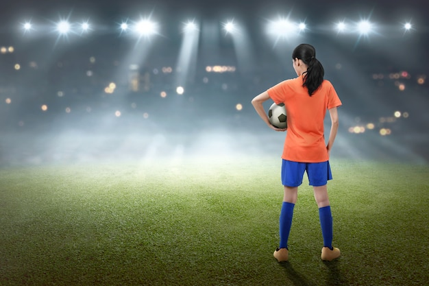 Hintere ansicht des asiatischen weiblichen fußballspielers mit der kugel