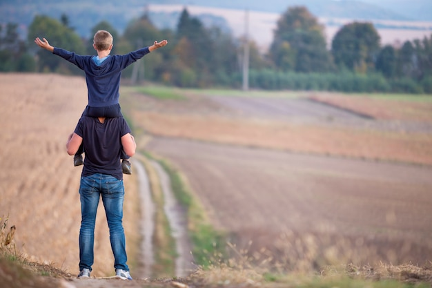 Hintere ansicht des athletischen vaters den schulternsohn weitermachend, der durch grasartiges feld auf unscharfen nebeligen grünen bäumen und blauem himmel geht.