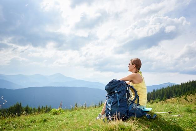 Hintere ansicht des attraktiven frauentouristen, der auf grasbewachsenem hügel mit rucksack und trekkingstöcken ruht