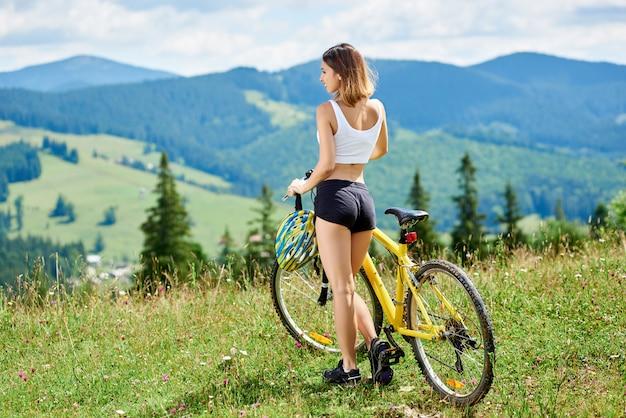 Hintere ansicht des attraktiven weiblichen radfahrers, der mit gelbem mountainbike auf einem gras steht und talblick am sommertag genießt