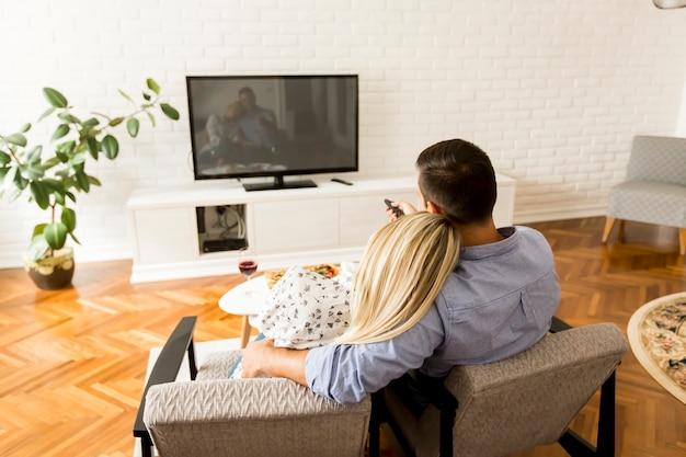 Hintere ansicht des beobachtenden fernsehens der paare im wohnzimmer