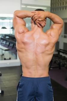 Hintere ansicht des bodybuilders aufwerfend in der turnhalle