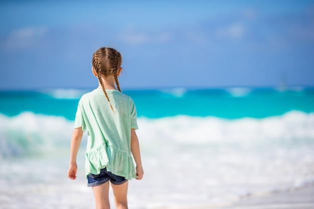 Hintere ansicht des entzückenden kleinen mädchens am strand