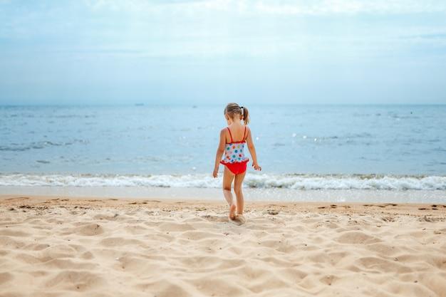 Hintere ansicht des entzückenden kleinen mädchens am weißen strand während der sommerferien