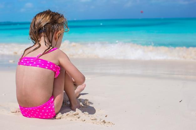 Hintere ansicht des entzückenden kleinen mädchens im badeanzug am tropischen strand