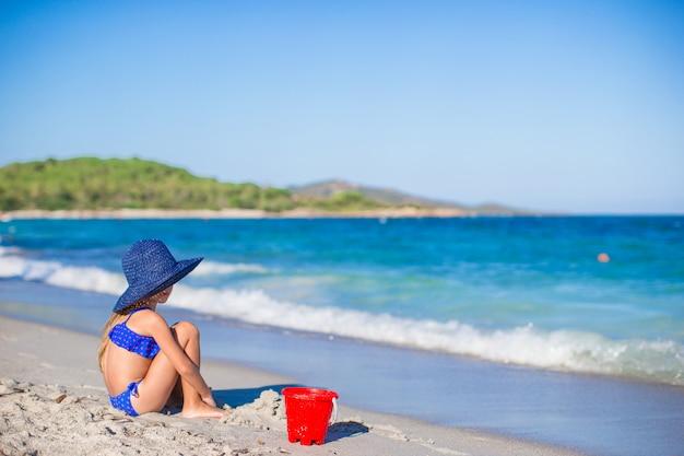 Hintere ansicht des entzückenden kleinen mädchens im großen blauen strohhut am weißen strand