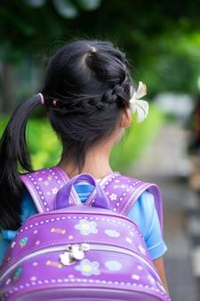 Hintere ansicht des entzückenden kleinen mädchens mit dem schönen haar gehend in den park