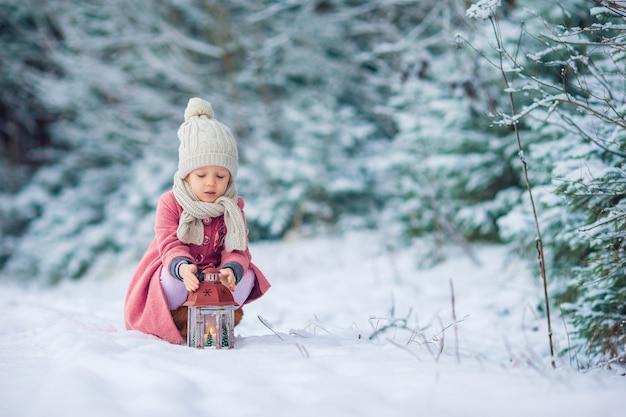 Hintere ansicht des entzückenden mädchens mit taschenlampe auf winter draußen