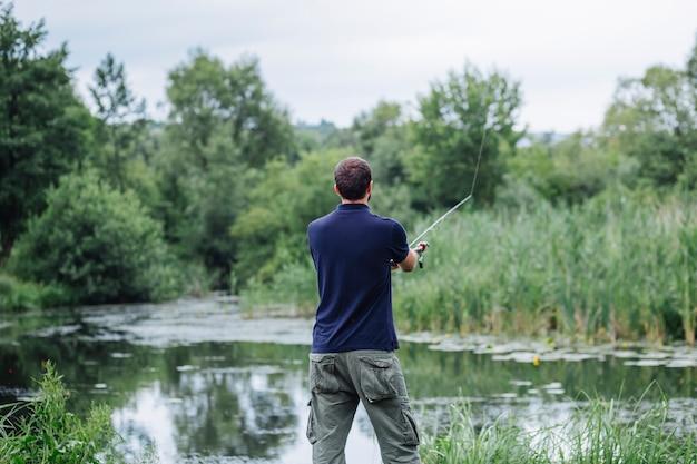 Hintere ansicht des fischens des jungen mannes im see