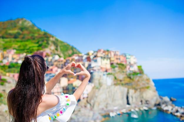 Hintere ansicht des glücklichen mädchens in einer schönen ansicht von manarola, cinque terre, ligurien, italien