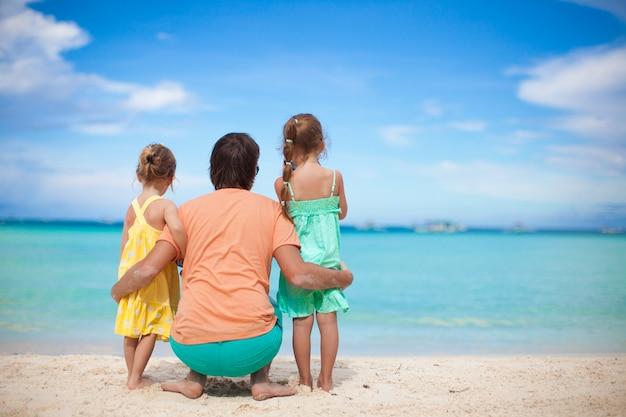 Hintere ansicht des glücklichen vaters mit seinen zwei töchtern auf tropischen strandferien