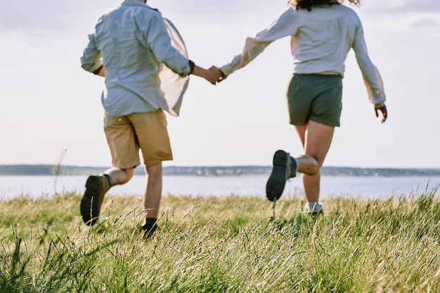 Hintere ansicht des glücklichen verliebten jungen paares, das grünes gras in richtung fluss oder see läuft, während wochenende im land verbringt