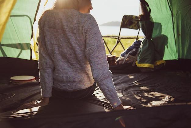 Hintere ansicht des glücklichen weiblichen touristen, der im campingzelt mit berg sich entspannt