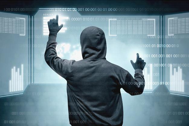 Hintere ansicht des hackers im schwarzen hoodie, der virtuellen bildschirm berührt