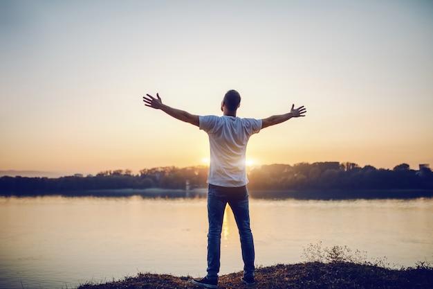 Hintere ansicht des hübschen kaukasischen mannes, der mit geöffneten armen auf klippe steht und fluss und schönen sonnenuntergang betrachtet.