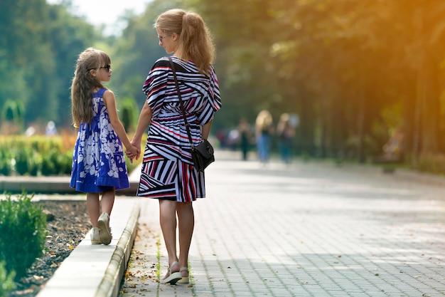 Hintere ansicht des jungen blonden langhaarigen dünnen attraktiven mädchens der frau und des kleinen kindes in der sonnenbrille und in den modischen kleidern gehend händchenhalten durch sonnige sommerparkgasse. happy family relations-konzept.