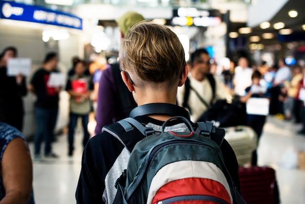 Hintere ansicht des jungen kaukasischen jungen, der in gedrängt am flughafen geht