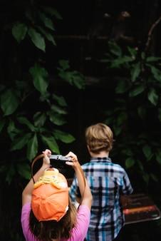 Hintere ansicht des jungen kaukasischen mädchens, das foto mit kamera macht