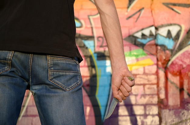 Hintere ansicht des jungen kaukasischen mannes mit messer in seiner hand gegen ghetto-backsteinmauer mit graffiti-gemälden