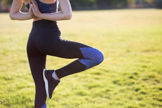 Hintere ansicht des jungen mädchens in yogaposition meditiert auf dem gebiet bei sonnenaufgang.