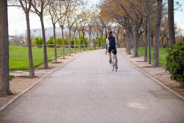 Hintere ansicht des jungen männlichen radfahrers in der sportkleidung und im schutzhelm, die fahrrad auf straße im park radfahren