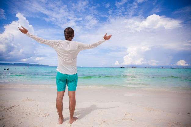 Hintere ansicht des jungen mannes breitete seine arme aus, die auf weißem sandigem strand stehen