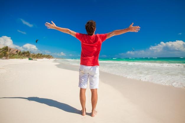 Hintere ansicht des jungen mannes breitete seine hände auf tropischem strand aus