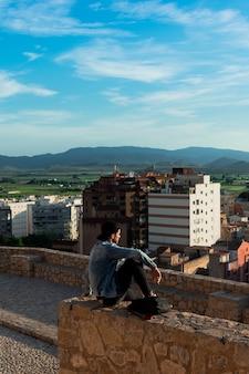 Hintere ansicht des jungen mannes stadt von der schlossdachspitze betrachtend. lifestyle und freiheit konzept.