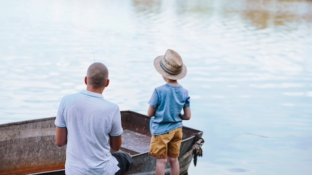 Hintere ansicht des jungen mit seinem vaterfischen