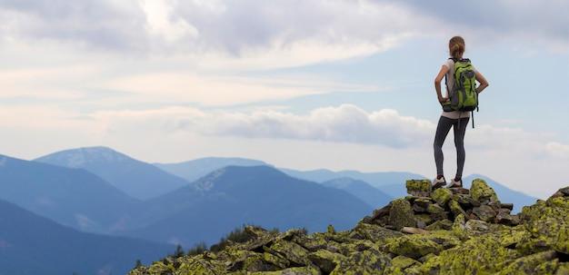 Hintere ansicht des jungen schlanken mädchens mit rucksäcken, die auf felsigem berggipfel gegen strahlend blauen morgenhimmel stehen, der nebliges gebirgspanorama genießt. konzept für tourismus, reisen und gesunden lebensstil.