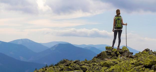 Hintere ansicht des jungen schlanken rucksacktouristen-touristenmädchens mit stock, der auf felsiger spitze gegen strahlend blauen morgenhimmel steht und nebliges gebirgspanorama genießt. tourismus-, reise- und kletterkonzept.