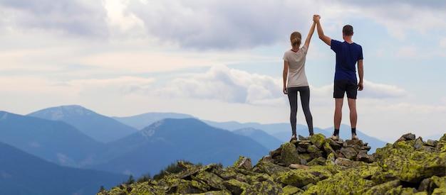 Hintere ansicht des jungen touristenpaares, des athletischen mannes und des schlanken mädchens, die mit erhobenen armen stehen, die hände auf felsigem berggipfel halten, das fantastisches panorama genießt. tourismus-, reise- und kletterkonzept.