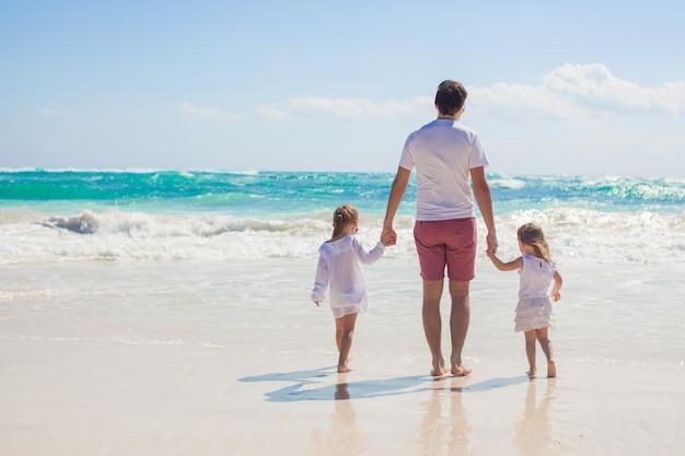 Hintere ansicht des jungen vaters und seiner entzückenden kleinen töchter, die auf weißen sandstrand am sonnigen tag gehen