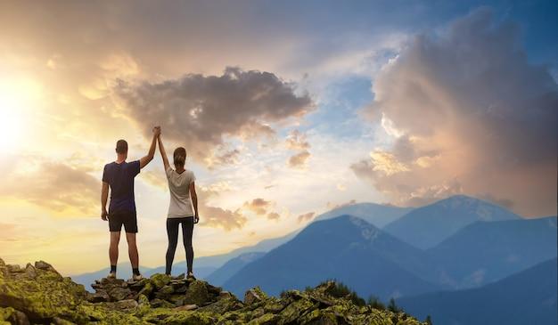 Hintere ansicht des jungen wandererpaares, das mit den erhobenen armen steht, die hände auf felsigem berggipfel halten und sonnenuntergangspanorama genießen.