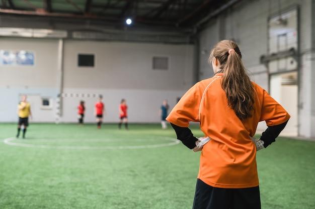 Hintere ansicht des jungen weiblichen torhüters in der sportuniform, die vor fußballspielern auf grünem feld steht