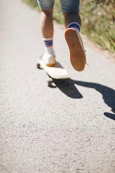 Hintere ansicht des kerls skateboard fahrend