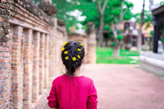 Hintere ansicht des kleinen asiatischen mädchens im roten kleid mit schönem haar und gelber blume, die im park gehen