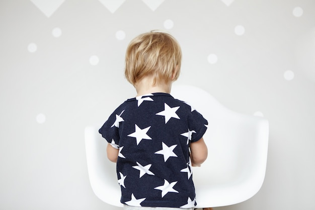 Hintere ansicht des kleinen kaukasischen jungen mit blondem haar, der t-shirt mit sternen darauf trägt und mit spielzeugen im kinderzimmer spielt. nettes kleinkind, das vor weißem stuhl steht und tag zu hause verbringt.